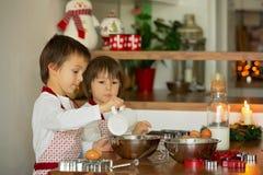 2 сладостных дет, братья мальчика, подготавливая печенья пряника Стоковое фото RF