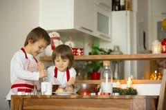 2 сладостных дет, братья мальчика, подготавливая печенья пряника Стоковые Фотографии RF