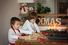 2 сладостных дет, братья мальчика, подготавливая печенья пряника Стоковая Фотография RF