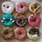 9 сладостных очень вкусных donuts с красочной поливой и ` надписи с днем рождения Стоковые Изображения RF