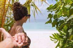 Следовать мной концепция молодой женщины идя к пляжу в тропическом назначении стоковые фотографии rf