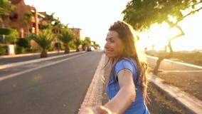Следовать мной - счастливая молодая женщина вытягивая руку парня - рука об руку бегущ на яркий солнечный день Shooted на различно акции видеоматериалы