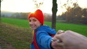 Следовать мной - счастливая молодая женщина в красной шляпе вытягивая руку парня Рука об руку идущ среди полей в сельской местнос сток-видео
