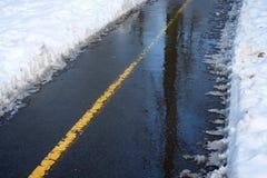 Следы в снеге на дороге асфальта зимы Стоковая Фотография