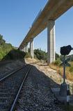 Следы железной дороги пересекая повышенный хайвей Стоковые Фотографии RF