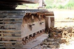 Следы крупного плана непрерывные или отслеживаемое колесо экскаватора или backhoe на поле почвы стоковые изображения
