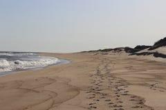 Следы ноги вышли в песок на песочном прибрежном пляже океана Стоковое Фото