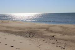 Следы ноги вышли в песок на песочном прибрежном пляже океана Стоковая Фотография
