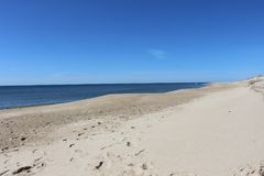 Следы ноги вышли в песок на песочном прибрежном пляже океана Стоковые Фото