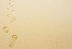 Следы ноги в предпосылке песка Стоковые Изображения RF