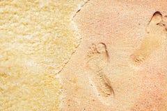 Следы ноги на пестротканом розовом песке на дезертированном пляже песок предпосылки тропический Стоковая Фотография RF