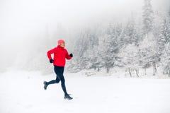 След девушки бежать на снеге в горах зимы Стоковая Фотография