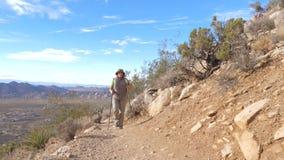 След женщины путешествия идет вверх по холму используя пеший поляка, вид спереди, замедленное движение акции видеоматериалы
