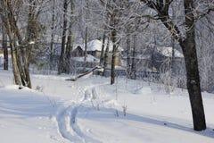 След лыжи на снеге водит к красивой деревне зимы стоковое фото