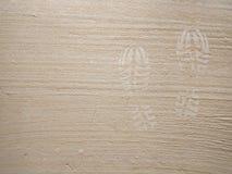 След ноги ботинка на серой конкретной поверхностной предпосылке песк стоковые изображения