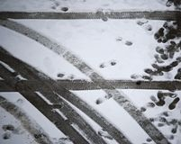 След ноги и трассировка колеса автомобиля на земле снега стоковые изображения rf