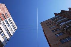 След самолета в небе Голубое небо и многоэтажные здания летая самолет на большую возвышенность o стоковое фото