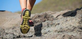 След спортсмена бежать в горах на скалистой местности стоковое изображение