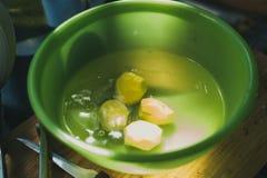 слезли картошки лежат в зеленом шаре с водой варить домодельные картошки стоковая фотография rf