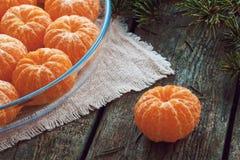 Слезли tangerines на плите на деревянных предпосылке и ели разветвляют Стоковое Изображение