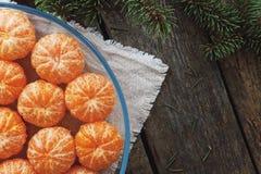 Слезли tangerines на плите на деревянных предпосылке и ели разветвляют Стоковое Изображение RF