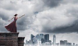 Слепая женщина в длинном красном платье наверху здания Мультимедиа стоковое фото