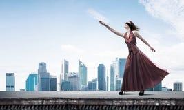 Слепая женщина в длинном красном платье наверху здания Мультимедиа стоковые изображения