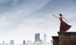 Слепая женщина в длинном красном платье наверху здания Мультимедиа стоковое изображение