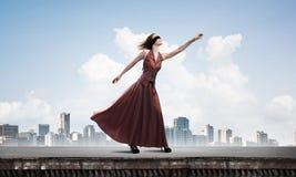 Слепая женщина в длинном красном платье наверху здания r стоковое изображение