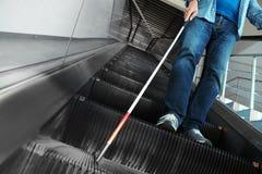 Слепой человек с длинной тросточкой на эскалаторе стоковое фото rf