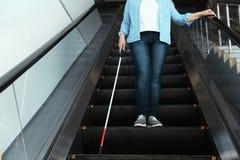 Слепой человек с длинной тросточкой на эскалаторе стоковое изображение