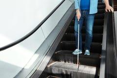 Слепой человек с длинной тросточкой на эскалаторе внутри помещения стоковые фото