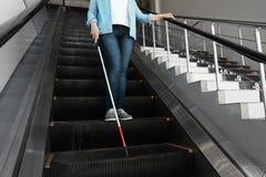 Слепой человек с длинной тросточкой на эскалаторе стоковое фото