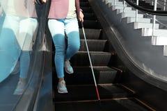 Слепой человек с длинной тросточкой на эскалаторе стоковое изображение rf