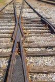 Сливать следов - 2 старых ржавых железных дорог придите вместе с немного листьев падения разбросанных среди гравия - выборочных стоковые фото