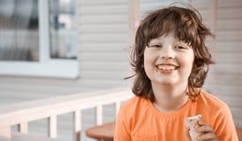 сливк мальчика есть счастливый льдед немного стоковая фотография