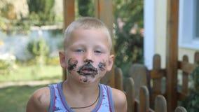 сливк ребенка ест льдед мальчик смазал его сторону с едой Ребенк есть мороженое от черного конуса вафли видеоматериал