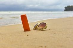 Сливк солнцезащитного крема, солнечные очки на морском побережье Стоковое Изображение