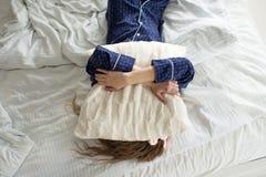 Слишком ленивый выйти кровати, женщина покрывает ее сторону с подушкой стоковое фото rf