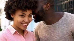 Слова африканского парня шепча влюбленности к подруге, счастливой усмехаясь паре стоковые изображения rf