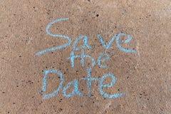 Слова сохраняют дату написанную с мелом тротуара на серой конкретной предпосылке стоковое фото