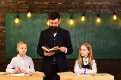 словесность урок литературы для 2 малых девушек с серьезным человеком учителя Литература и грамматика урок школы  стоковая фотография rf