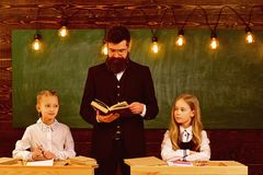 словесность урок литературы для 2 малых девушек с серьезным человеком учителя Литература и грамматика урок школы  стоковое фото rf
