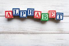 Слово - алфавит сказал по буквам с деревянными печатными буквами Стоковая Фотография
