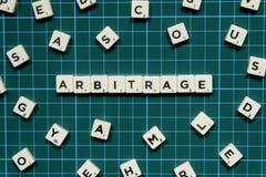 Слово арбитража сделанное из квадратного блока письма на зеленой квадратной предпосылке циновки стоковое фото rf
