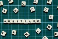 Слово арбитража сделанное из квадратного блока письма на зеленой квадратной предпосылке циновки стоковые изображения