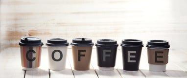Слово бумажного стаканчика кофе дальше на деревянном столе Стоковое фото RF