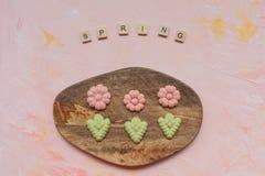Слово ВЕСНЫ и печенья цветка на деревянной доске на розовой предпосылке Праздники весны варя концепцию стоковые изображения rf