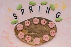 Слово ВЕСНЫ и печенья цветка на деревянной доске на розовой предпосылке Праздники весны варя концепцию стоковое фото rf