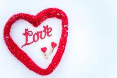 Слово влюбленности в снеге и 2 сердцах, в шарфе в разуме Стоковые Фотографии RF